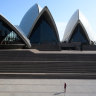A lone woman takes a photograph of the Sydney Opera House today.