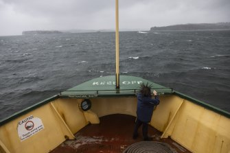 A child endures the wild weather aboard the Manly Ferry.