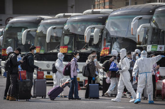 Chinese health officials in protective suits process Wuhan travellers going into 14-day quarantine on arrival in Beijing on Wednesday.
