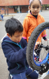 Budding mechanic Huy Ho, 8, from Flemington Primary School repairs a bike.