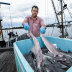 Fisherman Wayne Dredge unloads a catch of shark from his boat atSan Remo.
