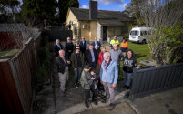 Micaela, front left, with baby daughter Harper, Brother Harry Prout, front right, and some of the 60 volunteers and donors, at one of four renovated Heidelberg West houses.