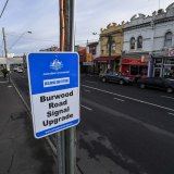 """A Commonwealth government sign promoting a """"signal upgrade"""" in Burwood Road, Hawthorn."""