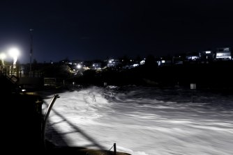 Waves are lit by the lights of the Clovelly Surf Club as a large south- east swell coincides with a high tide on Friday night.
