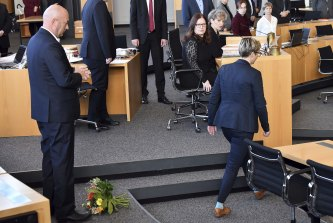 Die Linke's Susanne Hennig-Wellsow, right, walks away from Thomas Kemmerich of the Free Democrats after throwing a bouquet of flowers in front of him in Erfurt, Germany.
