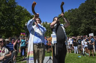 Rabbi Joshua Fixler, right, of congregation Emmanuel in Houston, and cantor Jason Kaufman of Bethel Hebrew congregation of Alexandria, Virginia, face the White House and blow shofars (ram's horns) as Jewish, interfaith and immigrant groups rally to commemorate the Jewish day of mourning by calling on the Trump administration to change its immigration policies.