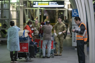 Passengers are assisted at Sydney International Airport before being transported to a hotel for quarantine.