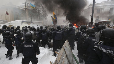 Riot police destroy a tent camp installed by activists of the Movement of New Forces, the political party led by Mikheil Saakashvili, as protesters burned tyres in Kiev, Ukraine early on Saturday.