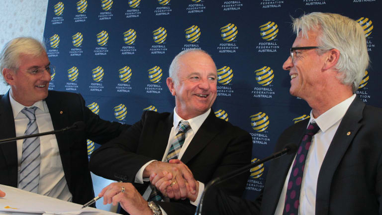 Graham Arnold shakes hands with FFA CEO David Gallop as FFA Chairman Steven Lowy looks on during a press conference to announce Arnold's appointment.
