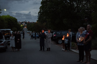 Neighbours stand along Buxton Street with lanterns and torches.