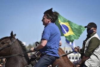 Brazilian President Jair Bolsonaro, on horseback, greets supporters outside the presidential palace in Brasilia on Sunday.