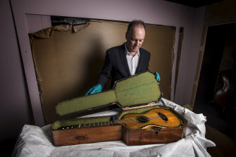 Dr Matthew Stephens removes the guitar, which is made of a satin wood veneer inlaid with ivory and mother of pearl, from its case as the show is installed.