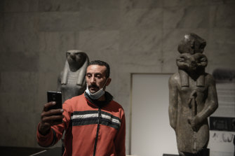 A visitor takes a selfie with pharaonic statues inside the new National Museum of Egyptian Civilisation in Cairo. The new museum has opened its  doors ahead of launching a display of 22 royal mummies that were previously housed in the Egyptian Museum near Tahrir Square.