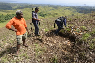 Willy Basi, a village elder from Mt Austin, guides members of the Royal Solomon Islands explosive ordnance disposal (EOD) team to a cache of 69 American mortars on site since 1942. The mortars are primed and ready to detonate.