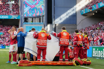 Medics and the Danish soccer team surround Christian Eriksen on the pitch after he suffered a medical emergency.