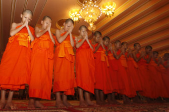 The Wild Boars pray during a ceremony marking the completion of their service as novice Buddhist monks.