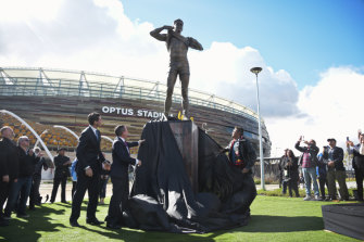 Winmar, right, AFL chief executive Gillon McLachlan, and WA Premier Mark McGowan unveil the statue of the player outside Optus Stadium in Perth.