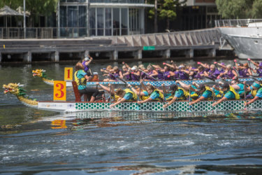Diane Edmondson (paddling fourth from left) and granddaughters Charlotte (paddling far left) and Ella (paddling second from left) competing for Brave Hearts dragon boat club at Docklands.