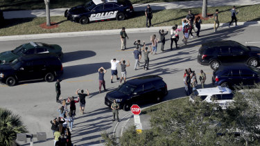Students hold their hands in the air as they are evacuated by police from Marjory Stoneman Douglas High School in Parkland, Florida after shooting.