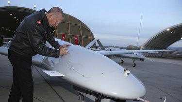 Turkey's President Recep Tayyip Erdogan signs a drone at a military airbase in Batman, Turkey, on Saturday.