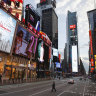 A police officer walks across an empty Seventh Avenue in a sparsely populated Times Square in New York.