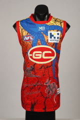 "The Suns' colours feature on the jumper, but they're also traditional colours with yellow representing women and red representing men.  ""They're both coming together on the one guernsey to represent our community,"" said designer Luther Cora."