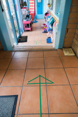 At Florence Rd. Pre School, tape on the ground indicates where parents and children should queue. A teacher lets students in one by one.