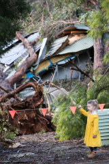 Mirrah, 6, looks at the damage after three huge trees landed on the roof of the Monbulk Aquatic Centre, where she was planning have her birthday party next week.