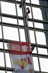 French 'spiderman' climber Alain Robert scaled a 68-storey skyscraper in Hong Kong on Friday to hoist a flag symbolising reconciliation between China and the territory.