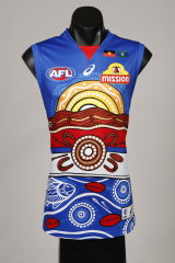 Brett Goodes is from the Adnyamathanha & Narungga people (South Australia), who are represented in the artwork with the sun rising on Akurra (giant water snake) moving and shaping the Ranges around him.
