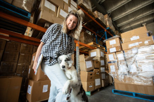 Silvia Hill and her most valuable employee in their warehouse, Luna the Border Collie.