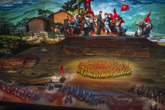 Performers take part in a historical routine in front of screen showing a painting of the late Chairman Mao Zedong.