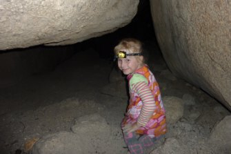 Kids love exploring the crawl-throughs on the Birrigai Time Trail at Tidbinbilla.