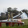 Firefighters inspect the crash scene near Moorabin Airport on Tuesday.