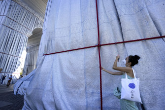 A visitor holds one of the red ropes holding the fabric in place.