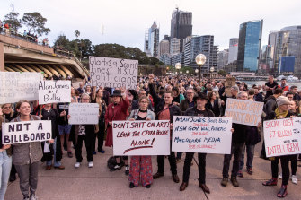 Protesters opposed to the Everest barrier draw being projected onto the Sydney Opera House display placards while at a forecourt rally.