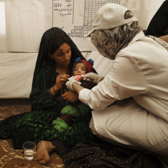 A medical staff member shows Gul Zada  how to feed her son ready-to-use food.