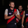 Michael Hurley (left) leads out the Bombers for their opening-round clash with Fremantle.