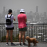 Visitors to the Mt Coottha lookout are seen as smoke haze as a result of bushfires blankets central Brisbane, Saturday, November 9, 2019. High temperatures and strong winds are creating extreme fire condition for parts of south east Queensland.