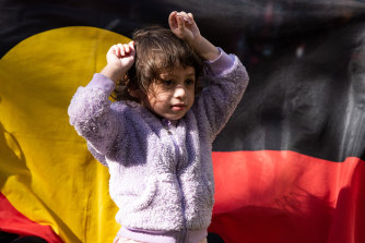 A young girl puts her fists up in the air in a sign of protest during a rally against Rio Tinto's decision to blast sacred Aboriginal sites in the Pilbara earlier this year.