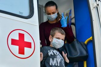 A boy and his mother leave a COVID-19 testing unit in Adygea, Russia.