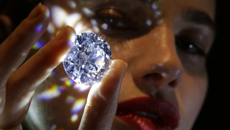 A 102.34, carat, D colour and flawless white diamond held by a model is displayed at Sotheby's auction house in London.