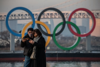 TOKYO, JAPAN - JANUARY 22: A couple wearing face masks check their phone after taking a selfie together in front of the Olympic Rings on January 22, 2021 in Tokyo, Japan. With just six months to go until the start of the Games, it has been reported that the Japanese authorities have privately concluded that the Olympics could not proceed due to the ongoing Covid-19 coronavirus pandemic. Spokesmen from the IOC and Japanese government have since rejected the report. (Photo by Carl Court/Getty Images)