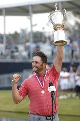 Jon Rahm celebrates with the US Open trophy.