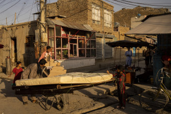 Two Afghan men push wheelbarrows loaded with furniture in Kharabat neighbourhood in Kabul, Afghanistan. A foundering economy, along with the coronavirus pandemic, has some families selling off furniture to get by.
