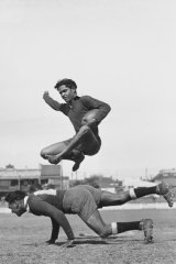 Player Mervyn William's brother Mick, 18, shows at practice the way he leaps over a tackling player. One of the images found in the lost archive.