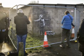 People take photographs through metal fencing, which has been erected to protect an artwork by street artist Banksy.