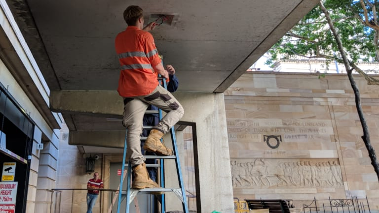 Contractors fix lighting in a Brisbane CBD laneway on Monday, after Mr Stone's death.