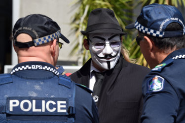 Police officers talk to an activist outside the Brisbane Magistrates Court. He was there to support G20 protesters.