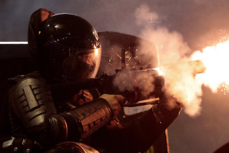 A police officer fires his tear gas launcher.